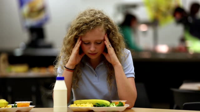niezadowolony młody nastolatek w szkolnej stołówce - stołówka filmów i materiałów b-roll