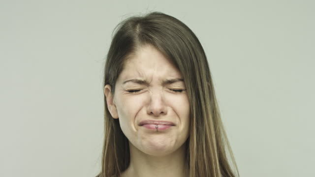 Upset young woman crying on gray background video