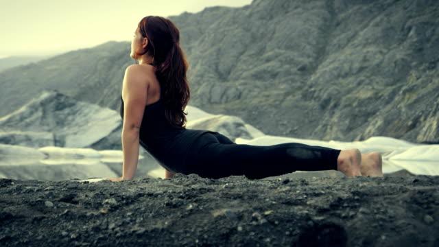 Upward facing dog pose. Woman doing yoga on glacier