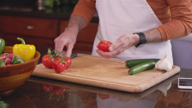 Upward panning shot of an old chef cutting a tomato video