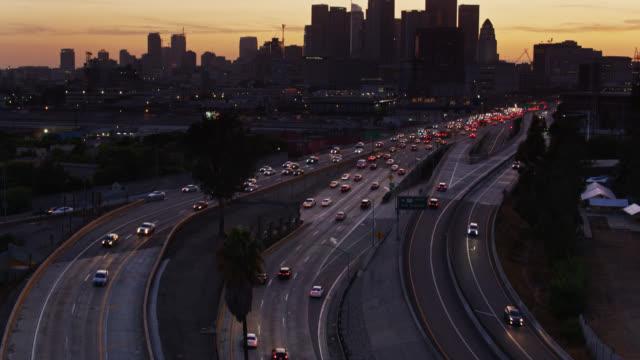Upward Tilting Shot of Freeway Ramp at Dusk with Downtown Los Angeles Skyline - Aerial - Vidéo