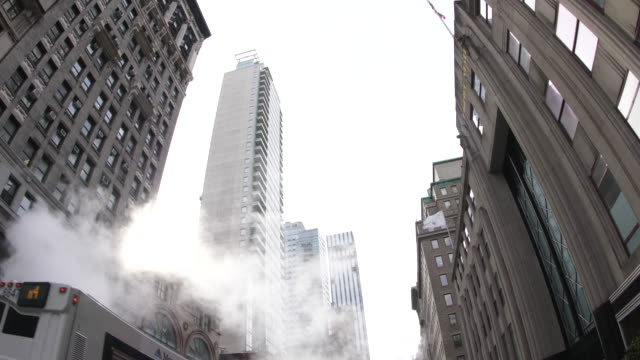 upward wide shot of steam smoke pipe in downtown, on traffic road in new york, usa. - fish eye video stock e b–roll