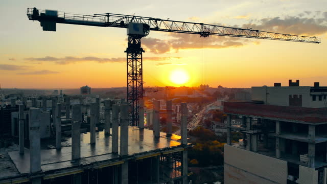 Urban buildings are getting constructed at sunset