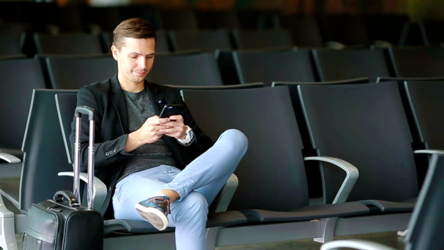Urban business man talking on smart phone traveling inside in airport. Casual young businessman wearing suit jacket. Handsome male model. Young man with cellphone at the airport while waiting for boarding video
