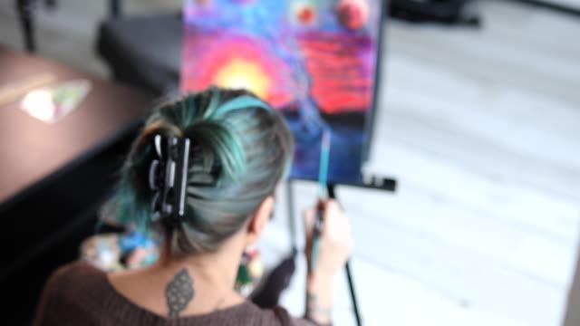 vidéos et rushes de peinture d'artiste femelle urbaine sur une toile avec des couleurs d'huile dans son atelier d'art - toile à peindre