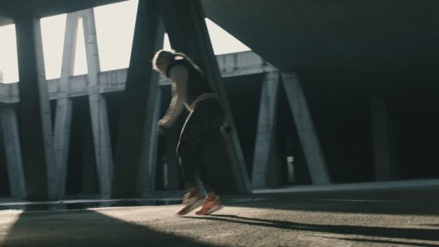 vídeos de stock, filmes e b-roll de corredora urbana feminina malhando em uma garagem na área urbana - resistência