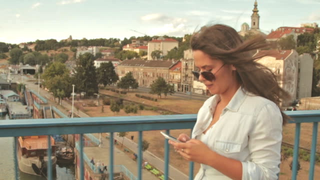 Urban girl walking and using cellphone on a bridge with city in background. video
