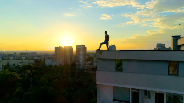 urban hero standing at the edge of a building roof at dusk - super hero stock videos & royalty-free footage