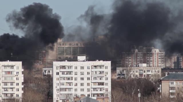 vidéos et rushes de le paysage urbain, le feu et beaucoup de fumée noire sort des bâtiments, maisons dans la ville, vue aérienne - desastre natural