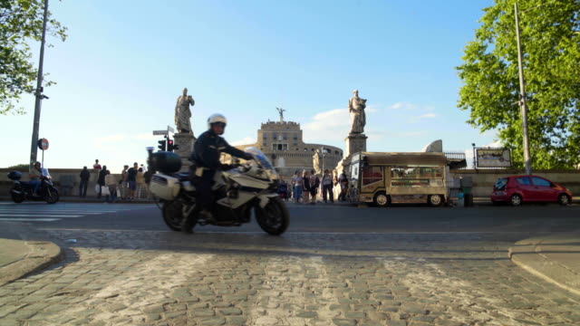 Urban life, motorcyclists riding past Mausoleum of Hadrian in Rome, tourism video