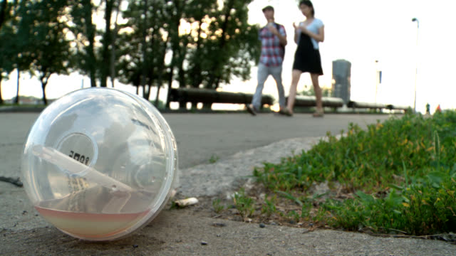 Urban litter trash plastic people walking by trash in foreground.  straw stock videos & royalty-free footage