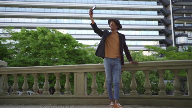 彼のソーシャルメディアのために自分撮りを取る都市の男性観光客 ビデオ