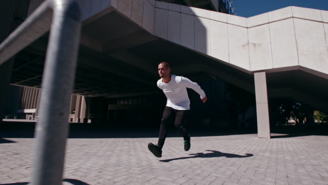 urban man doing parkour in city - parapetto barriera video stock e b–roll