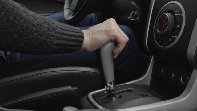 urban man uses transmission. man hand on automatic transmission car lever. driver man controls auto and switch gears. close up of gear shift in car. gearbox auto of manual transmission. car dashboard. - leva video stock e b–roll