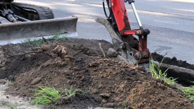 städtische kommunale traktor mit pfanne ist graben die kanalisation auf erdarbeiten. - handvoll stock-videos und b-roll-filmmaterial