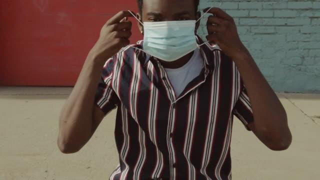 stockvideo's en b-roll-footage met stedelijke mensen zwarte man buitenshuis dragen gezichtsmasker tijdens pandemische virus uitbraak 4k video-serie - activiteit