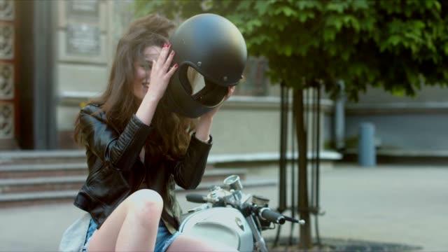 vídeos de stock e filmes b-roll de med urban portrait of a beautiful caucasian girl on a motorcycle. gorgeous brunette female in leather jacket, taking off motorcycle helmet, then laughs - helmet motorbike