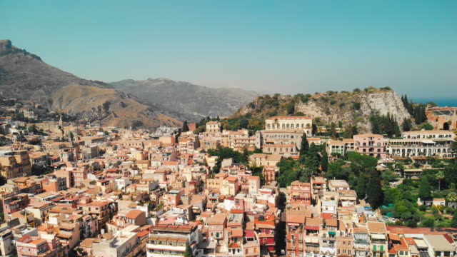 taormina, sicily, italy - august 2019: urban settlement near the rocky mountains and volcano. red roofs of houses and people walking in the streets. aerial drone shot - sicily filmów i materiałów b-roll
