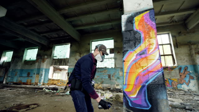 Urban street artist is painting graffiti in abandoned building with dirty walls and windows, he is using paint spray. Modern artwork and creative people concept. video