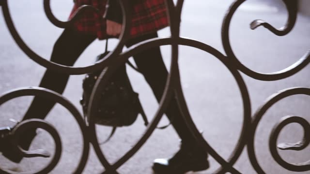 urban woman walking red skirt nylons boots Urban smart woman in short red tartan skirt walking behind wrought iron fence. Legs in nylons boots. Backpack in hands. short length stock videos & royalty-free footage
