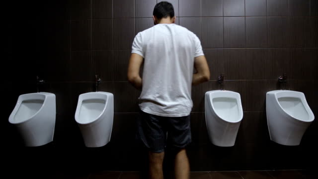 Urinals are fixed on a white wall Urinals are fixed on a white wall, gray tiles on the walls, brown floor tiles, taps for urinals silver metal. survey conducted indoors under fluorescent light bulbs, front view. wide angle, static household fixture stock videos & royalty-free footage
