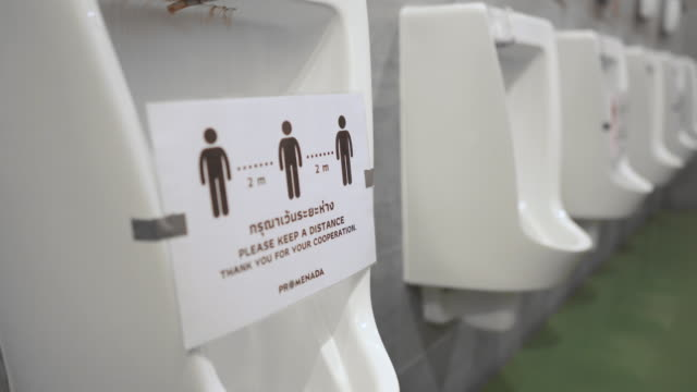 Urinals in men public toilet with social Distancing sign