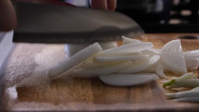 use a knife to cut the onions. - cebula filmów i materiałów b-roll