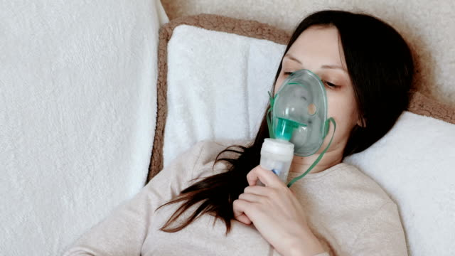 Use nebulizer and inhaler for the treatment. Young woman inhaling through inhaler mask lying on the couch. Side view. Use nebulizer and inhaler for the treatment. Young woman inhaling through inhaler mask lying on the couch. Side view medical oxygen equipment stock videos & royalty-free footage