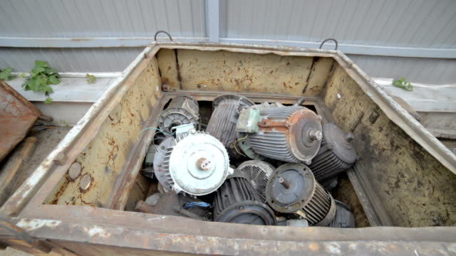 Used, broken and not working electric motors. Electric motors are piled in a metal container video