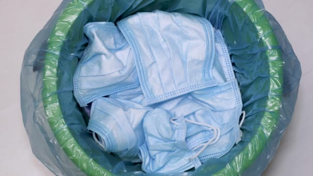used hygienic mask in the trash bin, infectious waste, prevented virus covid-19 by separating infected waste. face mask throwing into the bin. protectve waste after pandemic - удалять стоковые видео и кадры b-roll
