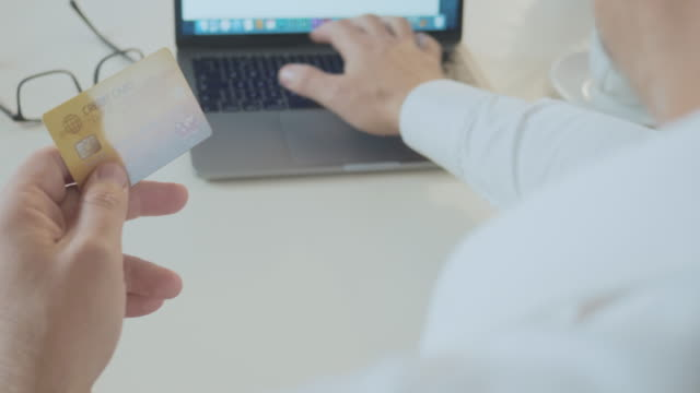 vídeos de stock, filmes e b-roll de usando um cartão de pagamento gold para pagamento online - costumer