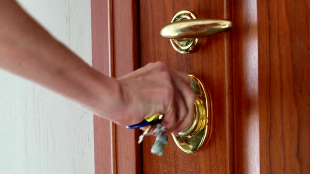 using a key to open the lock of the front door - mano donna dita unite video stock e b–roll