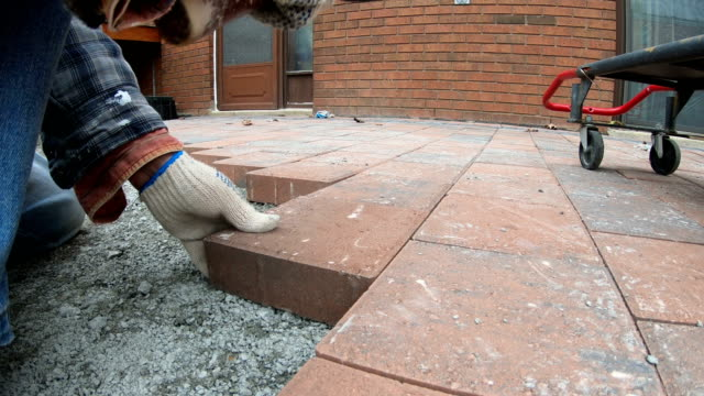 using a mallet to set paver - mattone video stock e b–roll