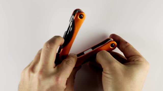 utilizzando un multitool - pinze attrezzo manuale video stock e b–roll