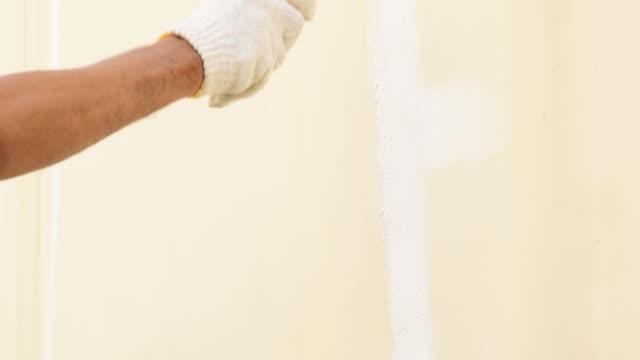 vídeos de stock e filmes b-roll de using a roller for painting white color on the concrete wall. - concrete wall interior