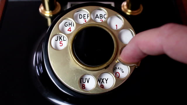 Using a Rotary Phone Dial - 2 Different Angles A man uses a rotary dial phone landline phone stock videos & royalty-free footage