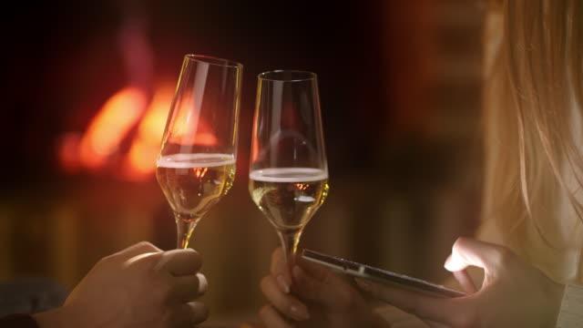 vidéos et rushes de using ms un téléphone intelligent tout en buvant un vin au coin du feu - flûte à champagne