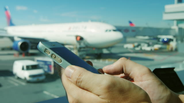 using a smartphone at the airport. in the background is seen the airfield and aircraft - fare una prenotazione video stock e b–roll