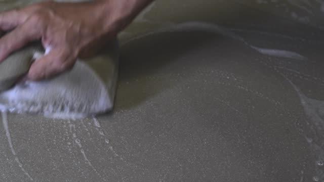 med hjälp av en svamp rengöring kakel golvet. - construction workwear floor bildbanksvideor och videomaterial från bakom kulisserna