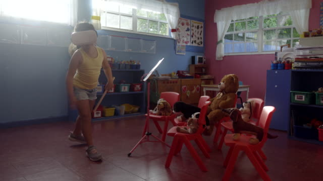 Using a virtual reality set pretending to be a orchestra conductor at pre-school