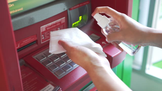 using alcohol based sanitizer spray on automated teller machine button for disinfecting - banks and atms stock videos & royalty-free footage