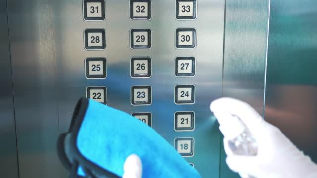 uso di spray disinfettante a base alcolica sul pulsante dell'ascensore per la disinfezione - pulito video stock e b–roll