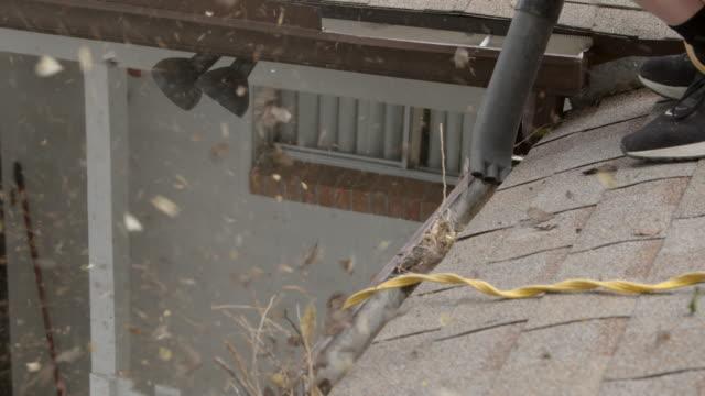vidéos et rushes de utilisation d'un souffleur de feuilles électriques pour enlever les graines d'orme, les feuilles et les bâtons des gouttières de toit en aluminium à la maison pour le nettoyage de printemps - vidéos de rallonge électrique
