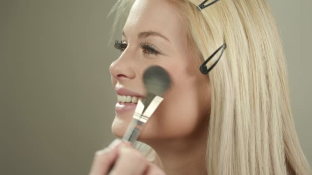 Using blush brush on cheeks