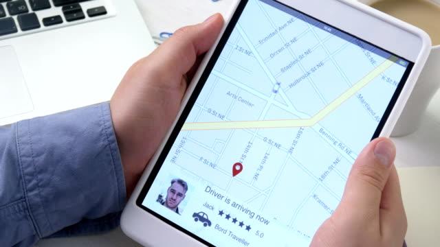 vídeos de stock, filmes e b-roll de usando o app sobre o tablet digital de compartilhamento de carros. homem chega para pegar seu passageiro - dividindo carro