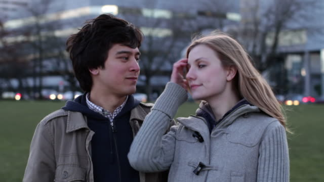 Using Chapstick Good looking young man and woman in conversation against the backdrop of the city at dusk.  Guy uses chapstick during this clip.  Recorded in downtown Portland, Oregon. lip balm stock videos & royalty-free footage