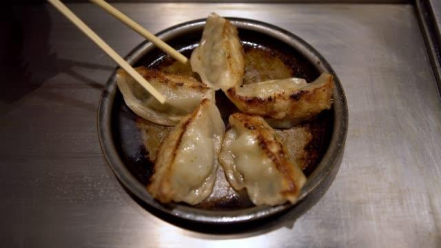 4K, Using chopsticks for eating fried dumplings in a restaurant. Guotie food