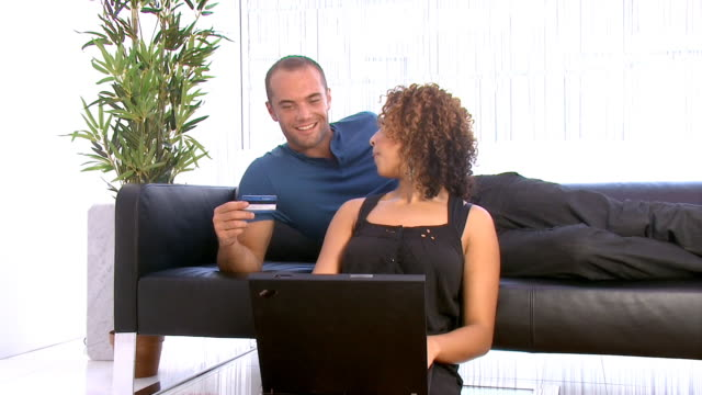 Using credit card online young couple in modern home video