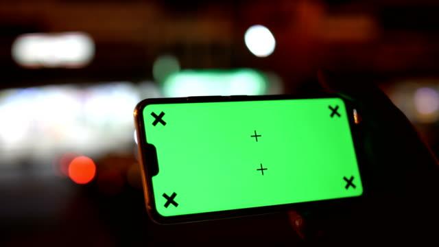 utilizzo dello smartphone digitale in modalità orizzontale con schermo verde con sfondo semaforo notturno, tasto chroma - composizione orizzontale video stock e b–roll