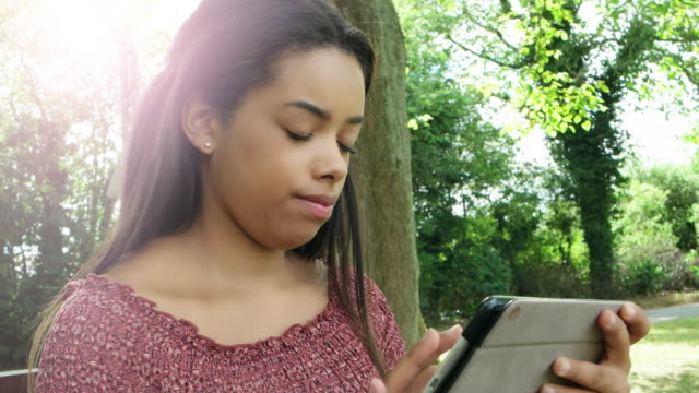 Using digital tablet, outdoors. Young woman. video